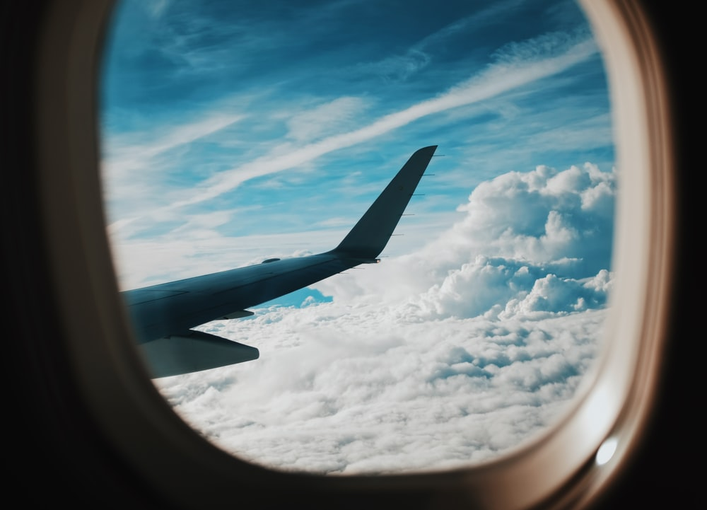 person taking picture of plane wings while flying during daytime