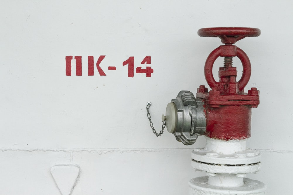 red and white fire hydrant beside white wall