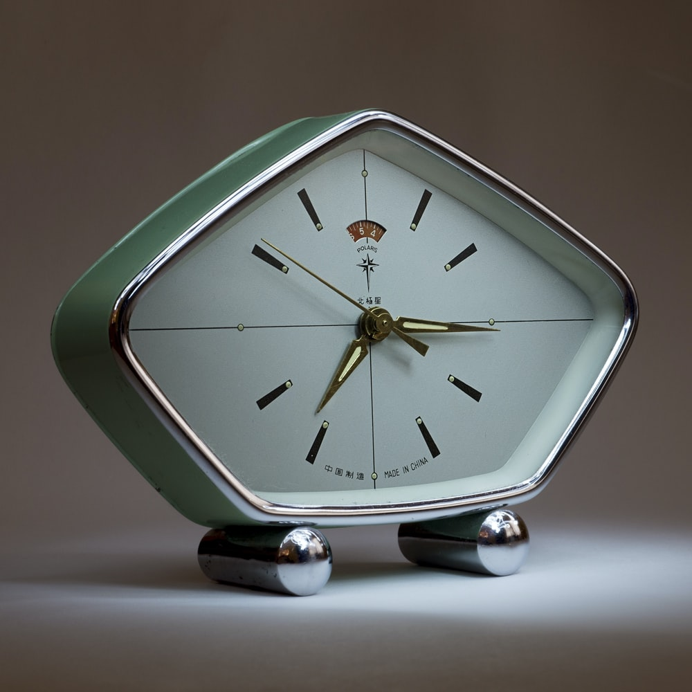 green analog clock at 3:37