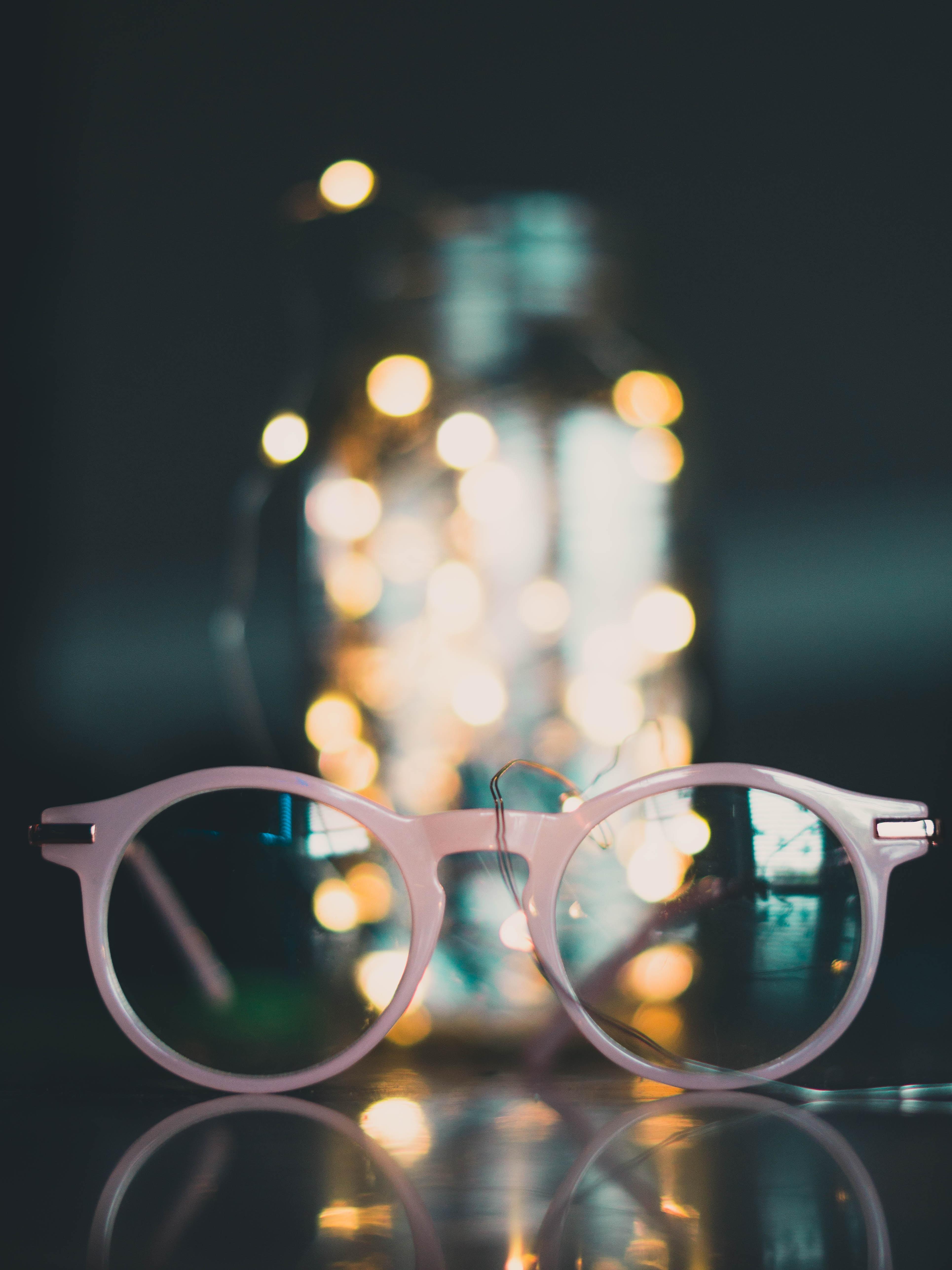 gray framed eyeglasses near glass jar