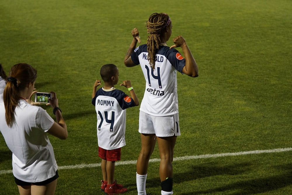 boy and girl soccer players standing on soccer field