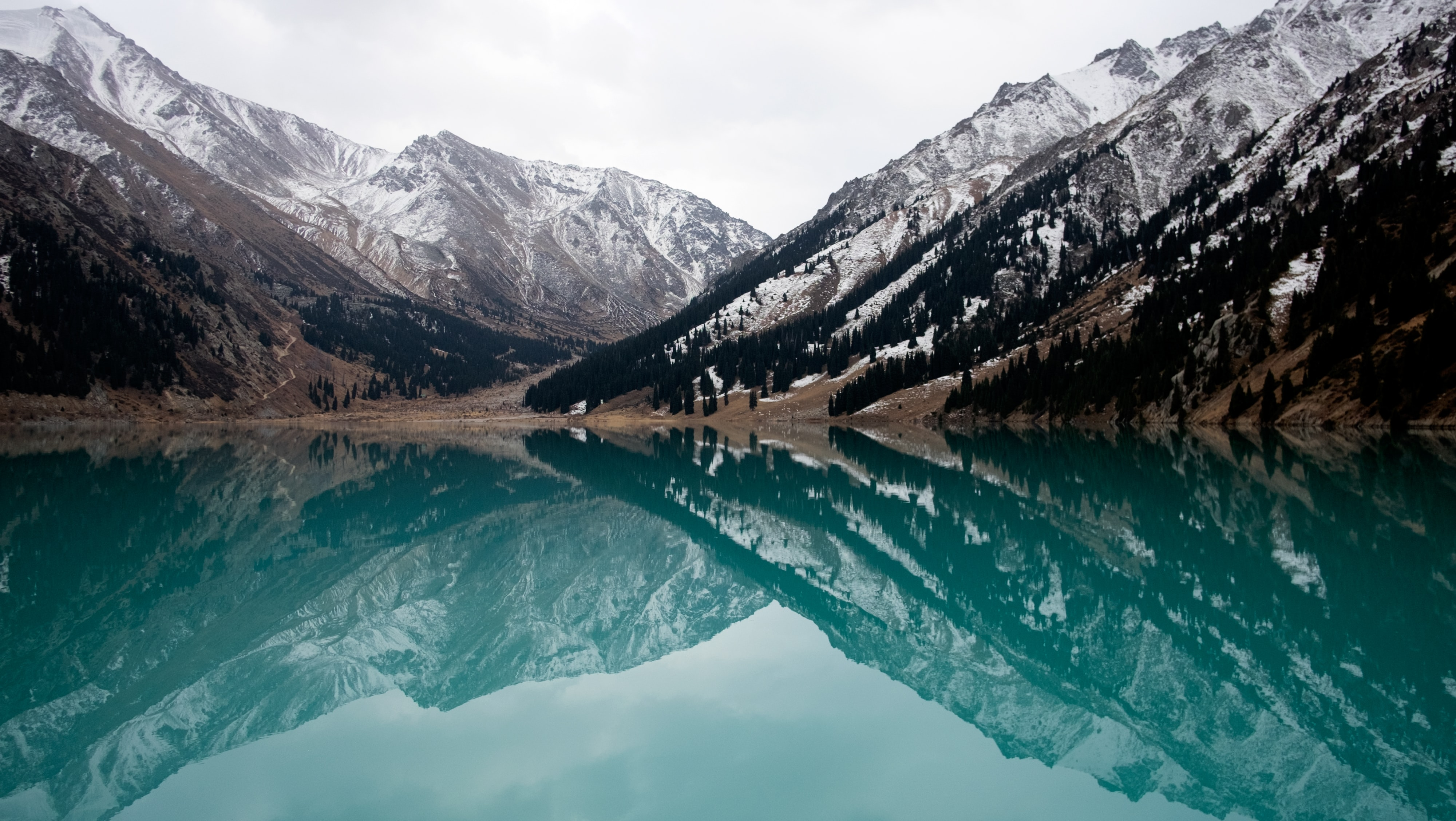 lake surrounded with mountains during daytime