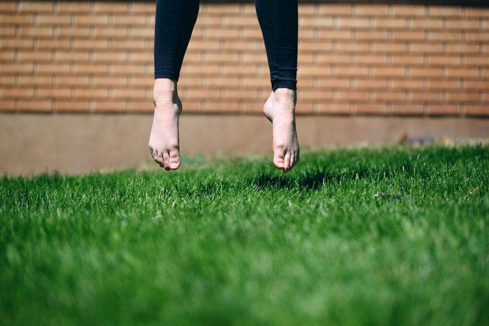 person jumping on grass outdoor