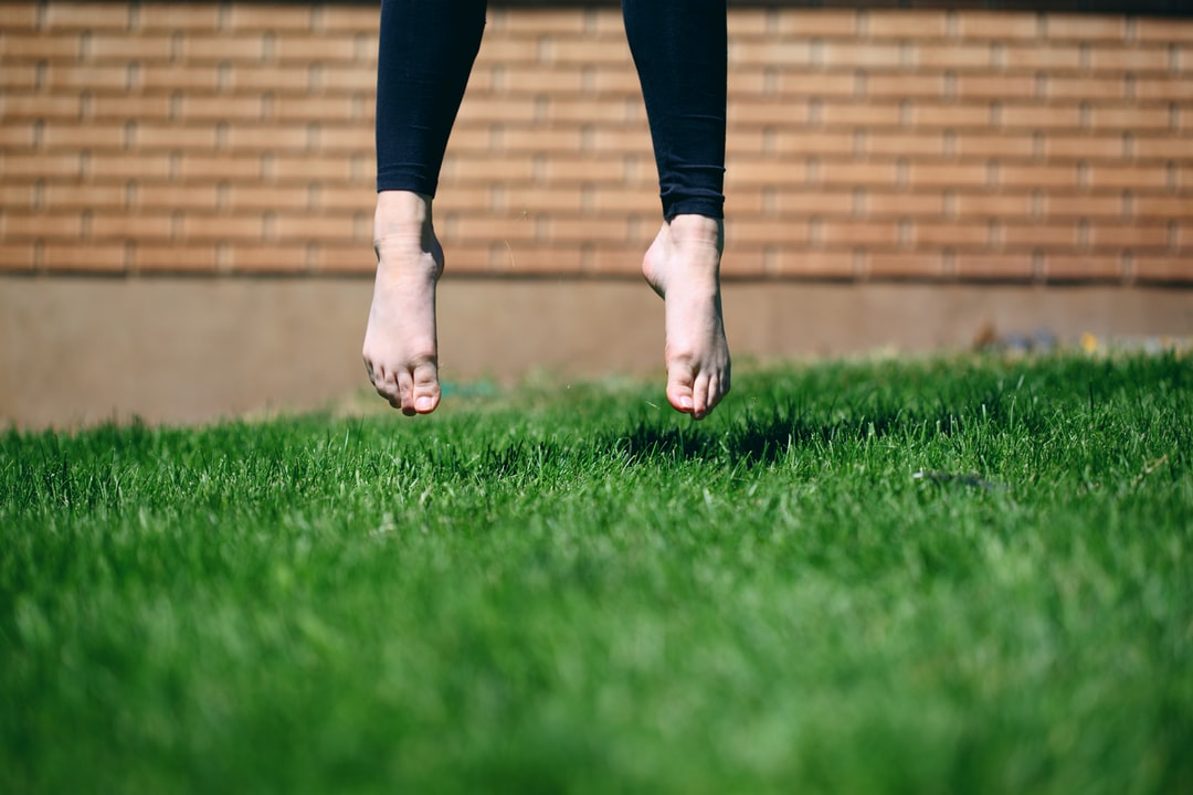 A person takes flight, barefoot in the green summer grass.