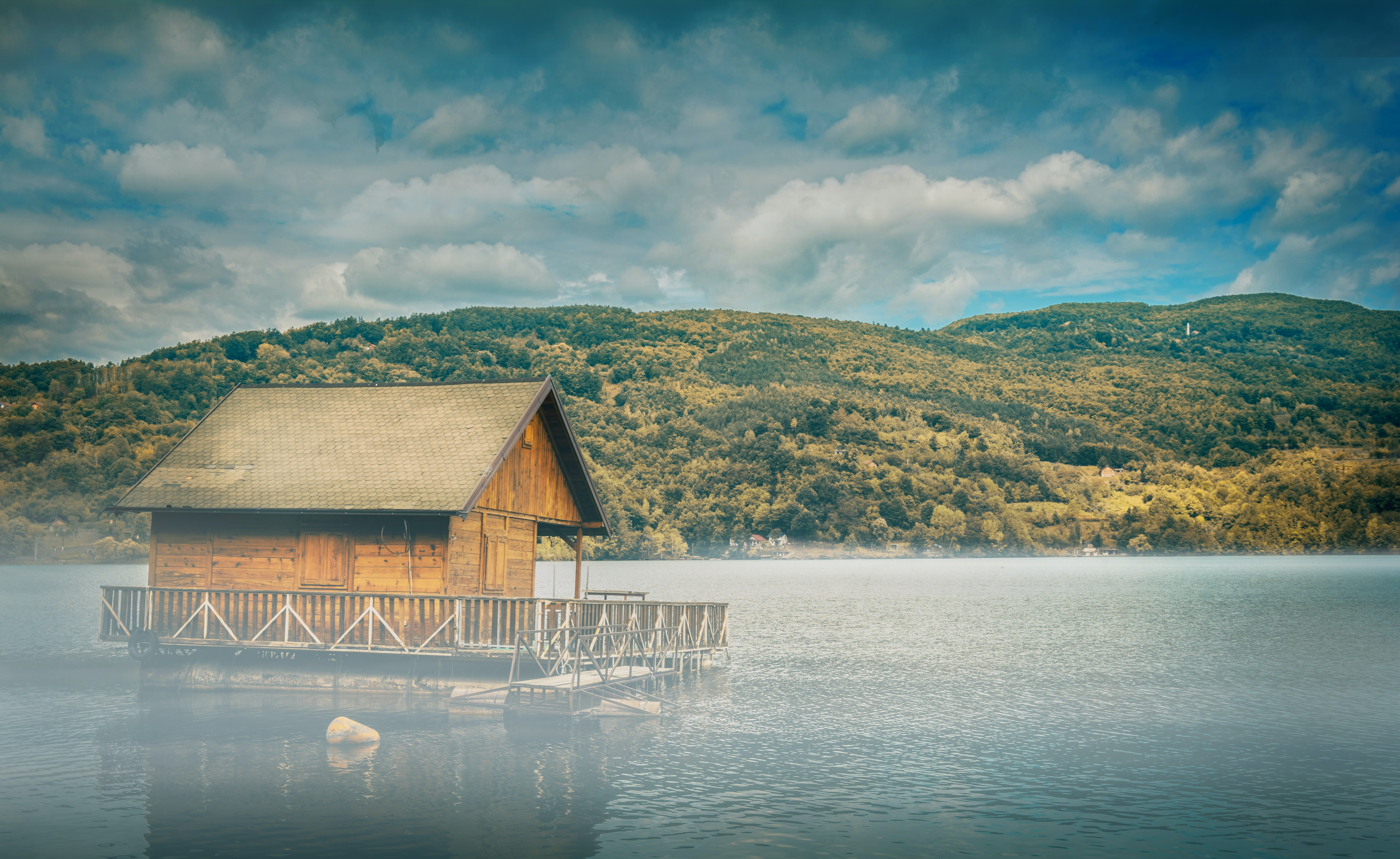 brown wooden floating cottage in middle of body of water with mountain in background
