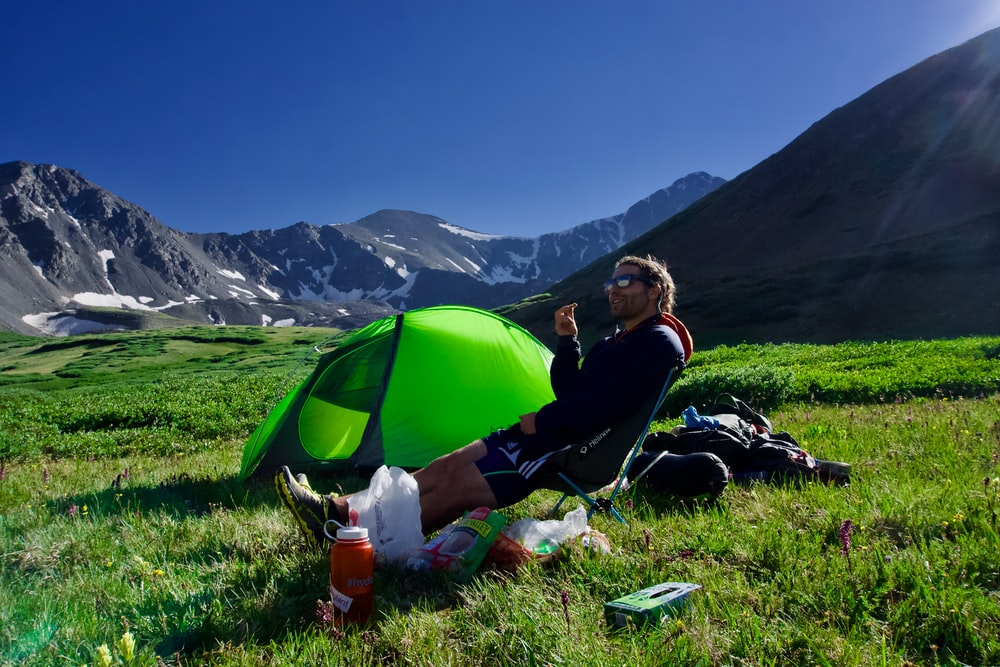 man sitting on black camping chair beside green dome tent