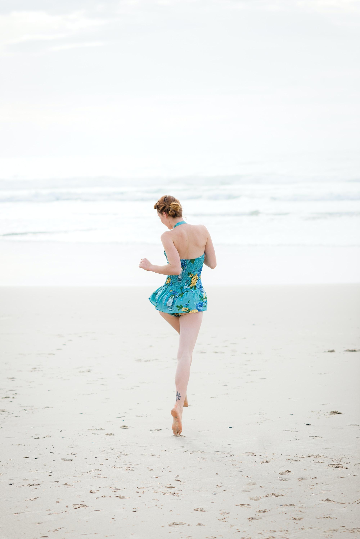 woman walking on shore near beach