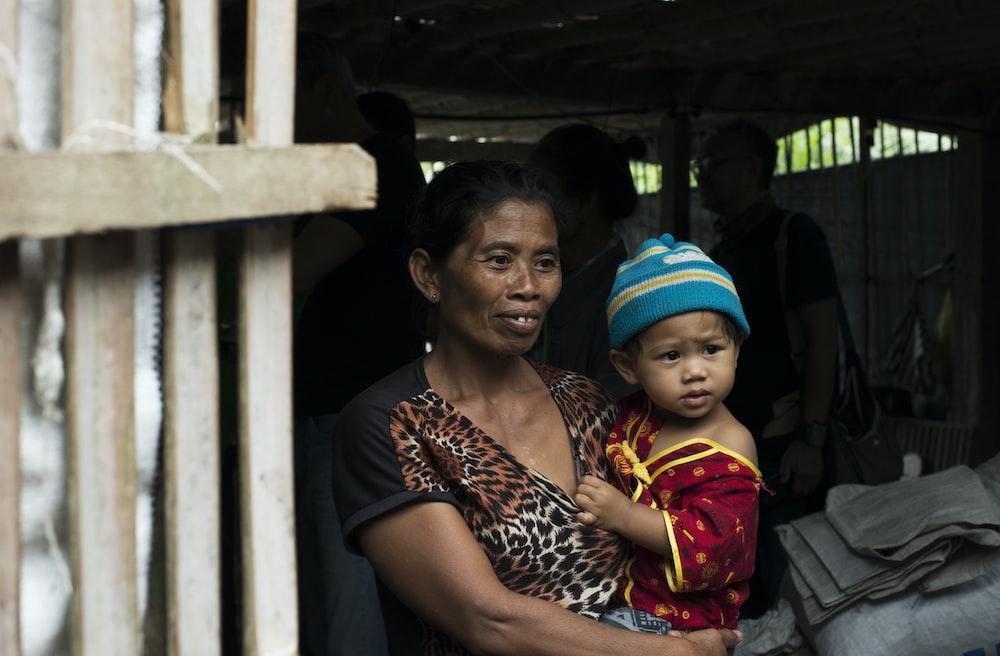 woman carrying child near door