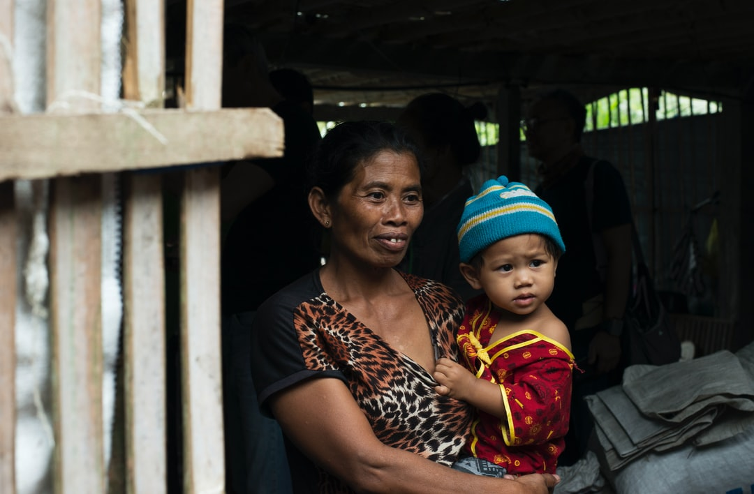 A mother and young child with happy yet desperate eyes as they receive donations at a local shelter. This photo was taken two days after Mount Agung on Bali erupted forcing the airport to close and thousands of villagers to flee into makeshift shelter centres. Bali, Indonesia 29 November 2017.