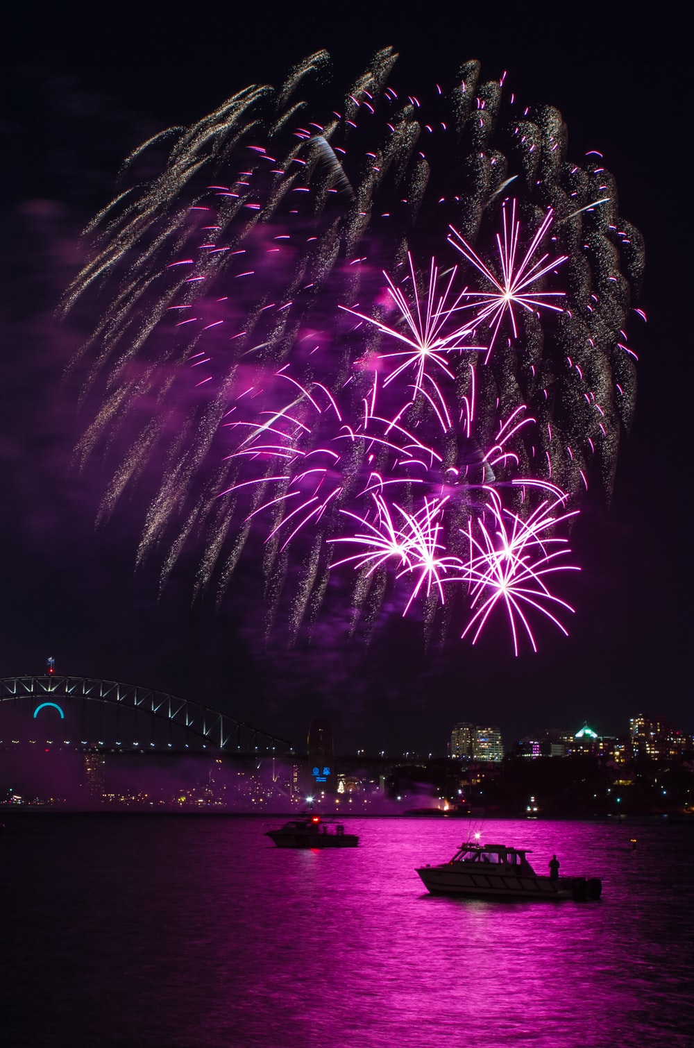two boats on sea under fireworks display