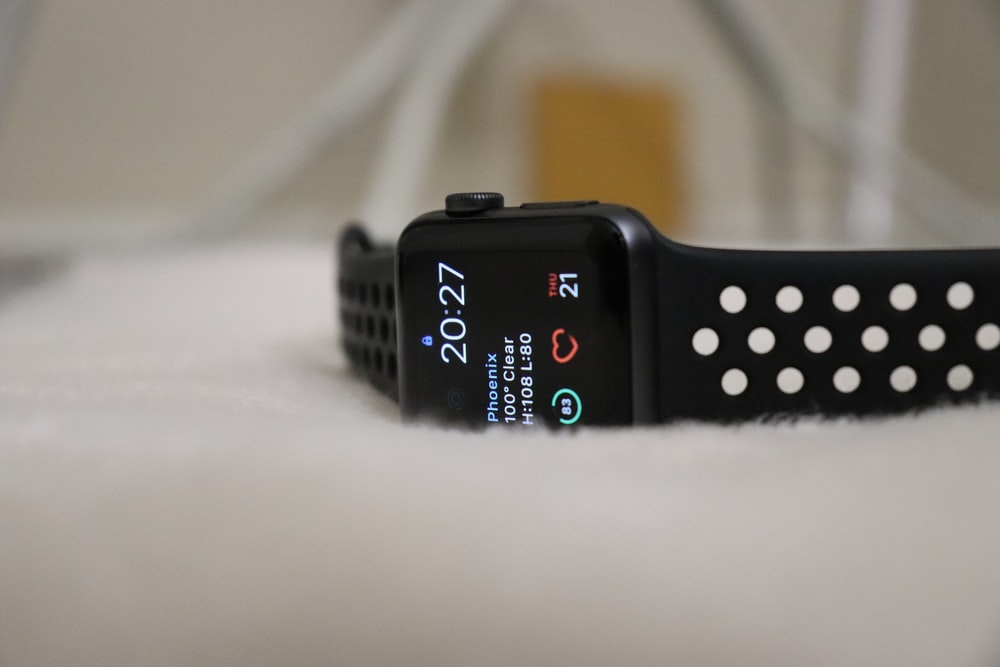 silver aluminum case Apple Watch with black Nike Fuel Band displaying 20:27