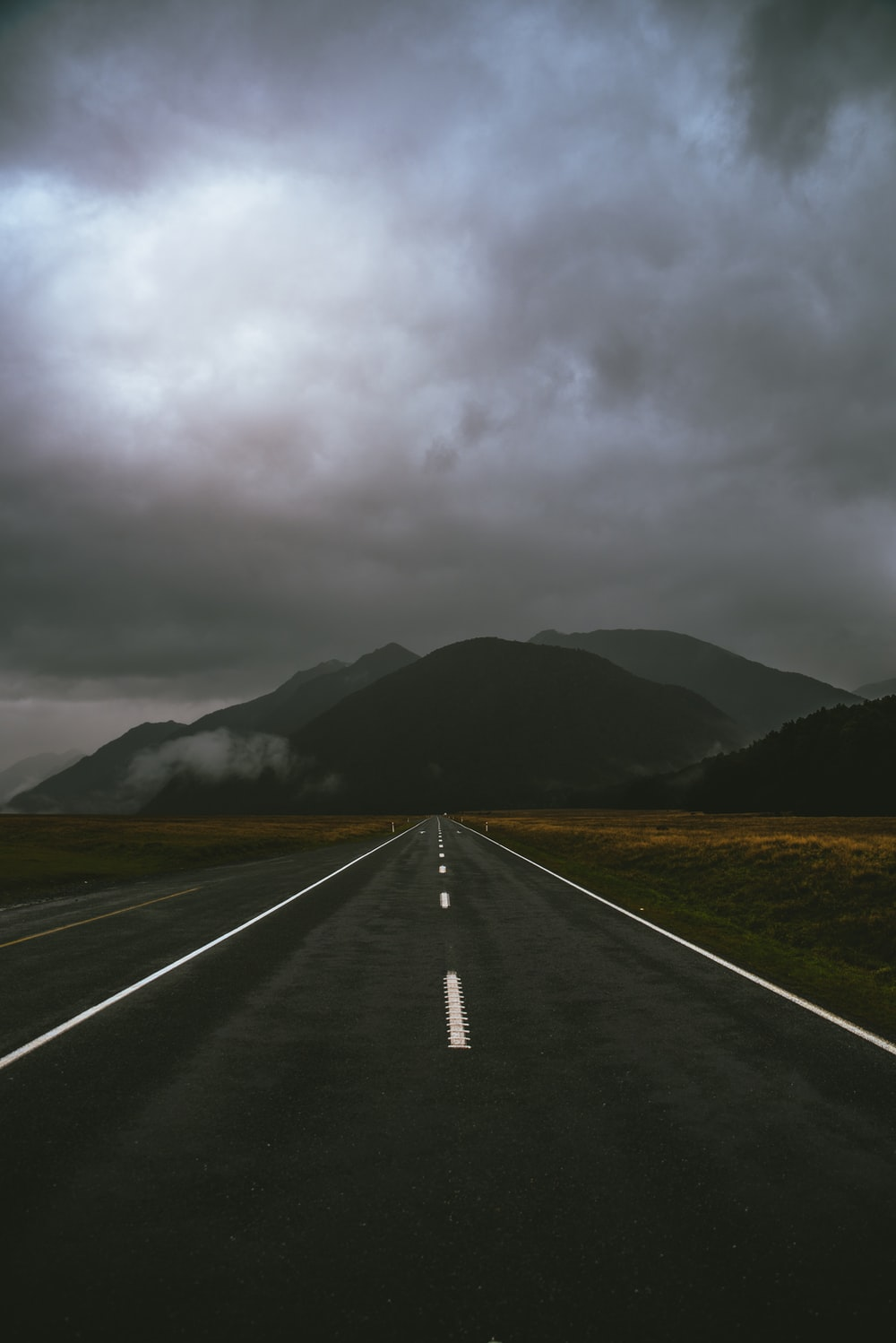 gray road under cloudy sky