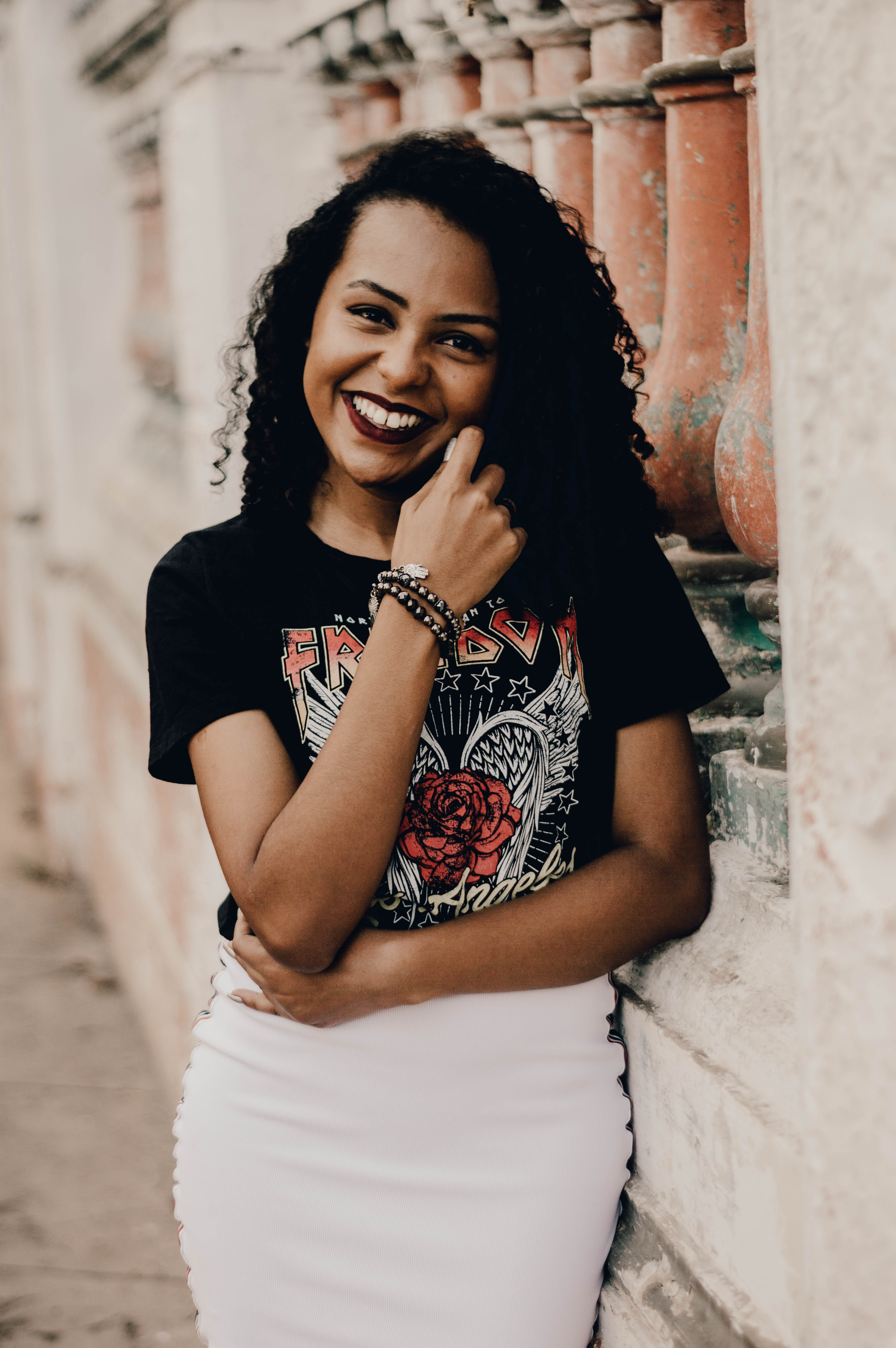smiling woman leaning on concrete wall