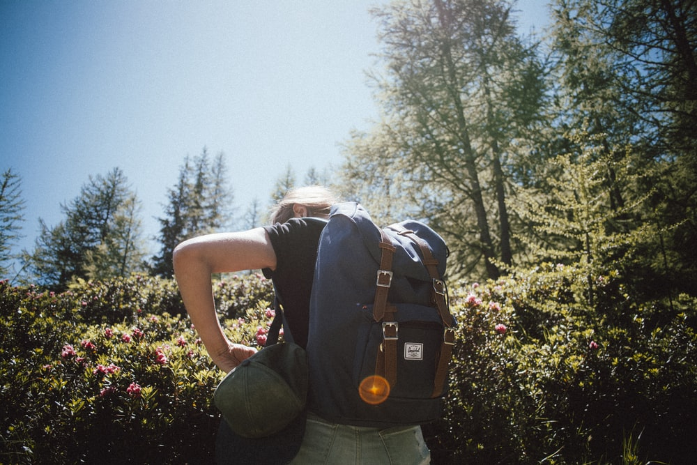 woman carrying bucket backpack facing backward