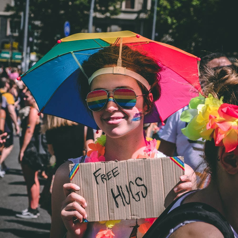 person holding Free Hugs signage