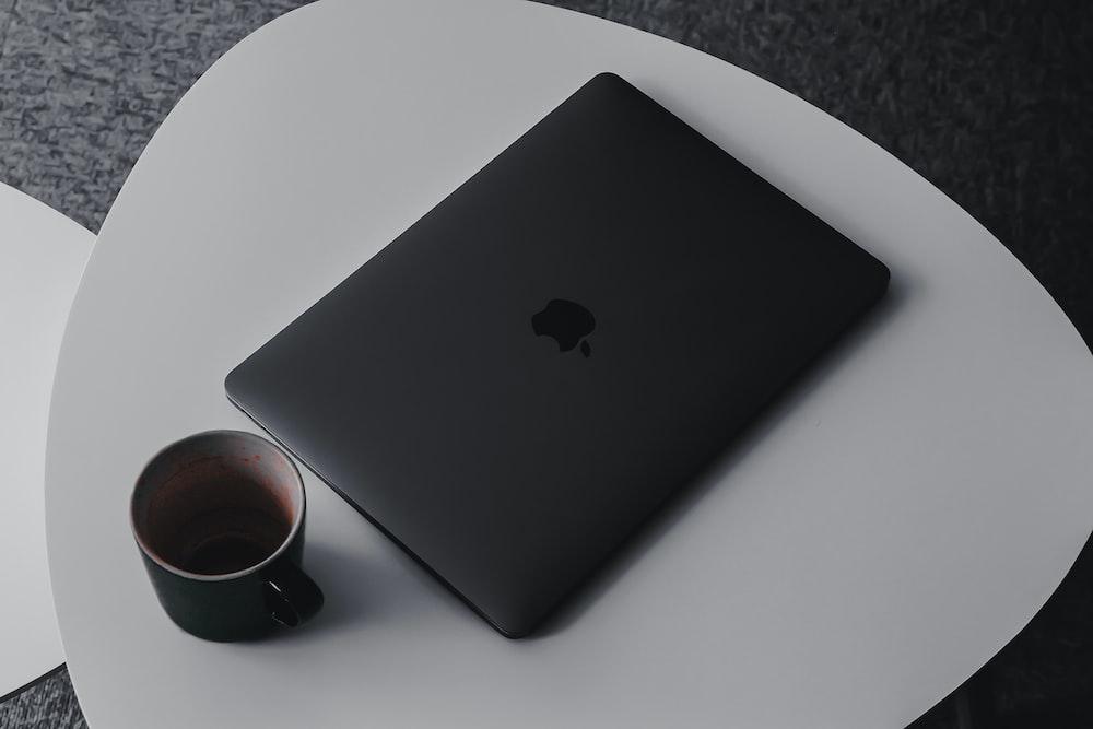MacBook Pro beside mug on table