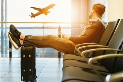 man sitting on gang chair with feet on luggage looking at airplane travel teams background