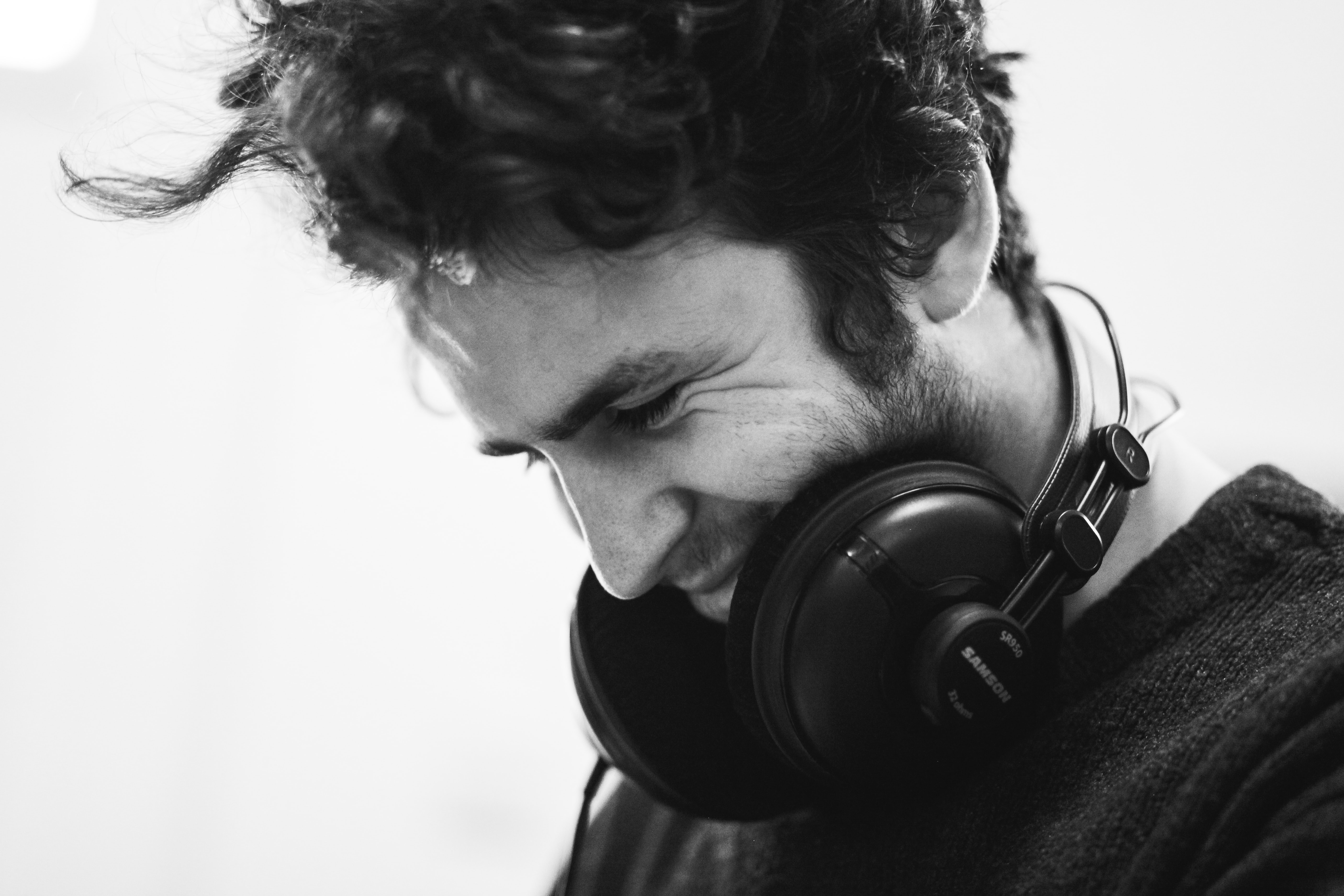 grayscale photography of man with headphones on neck