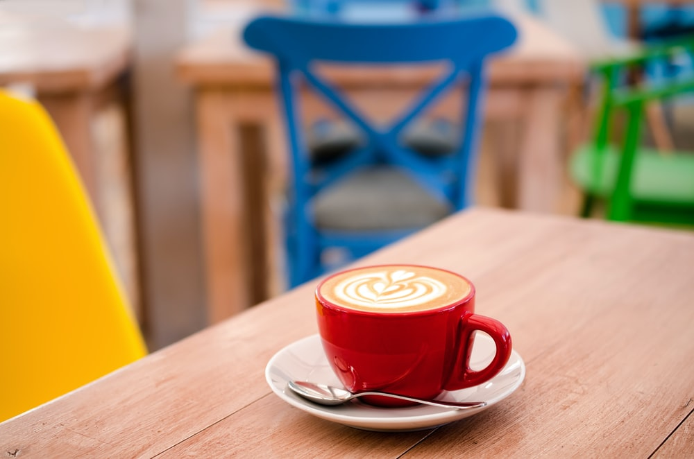 red espresso mug with white sauce on top wooden table