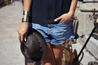 person wearing blue denim short shorts and holding black trilby hat