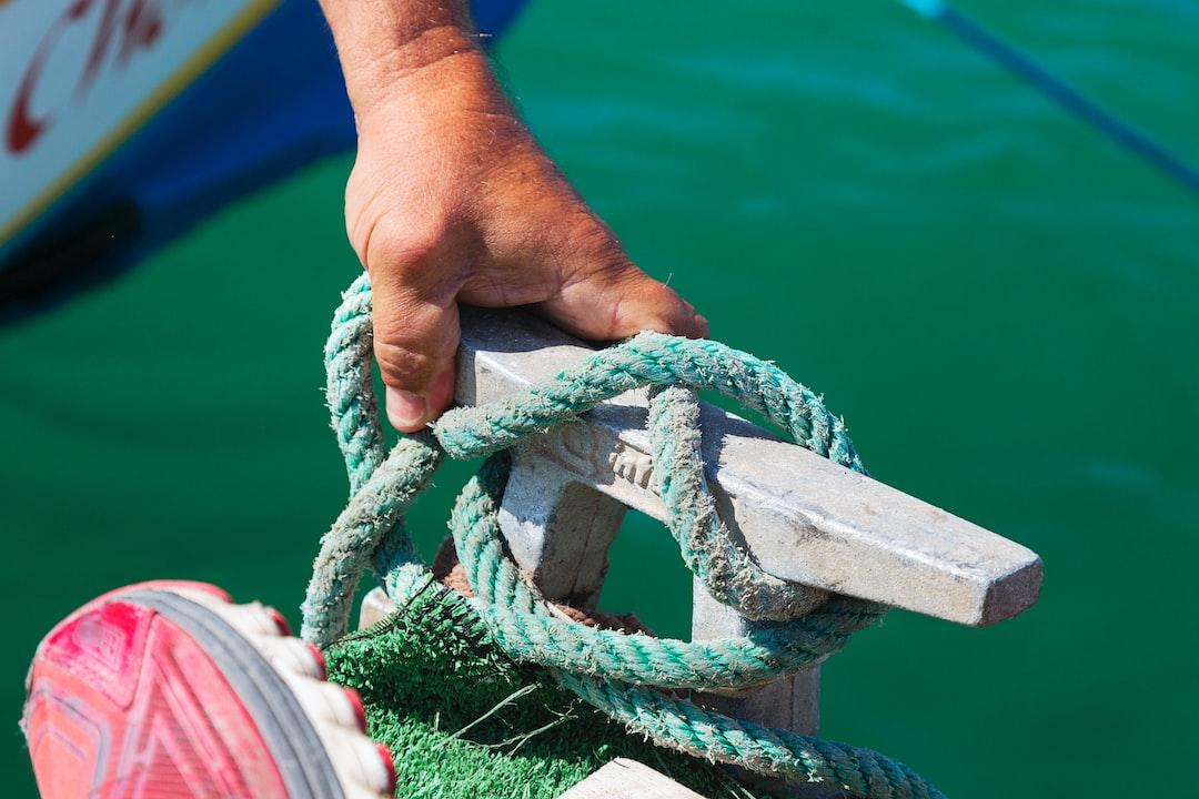 """Esta es la mano de un """"espailla"""" disponiéndose a arriar el cabo que fijaba la barca al  pantalán durante una regata de barcas de jábegas celebrada en el puerto de Málaga. Los lazos que fijan hay que desatarlos para poder avanzar."""
