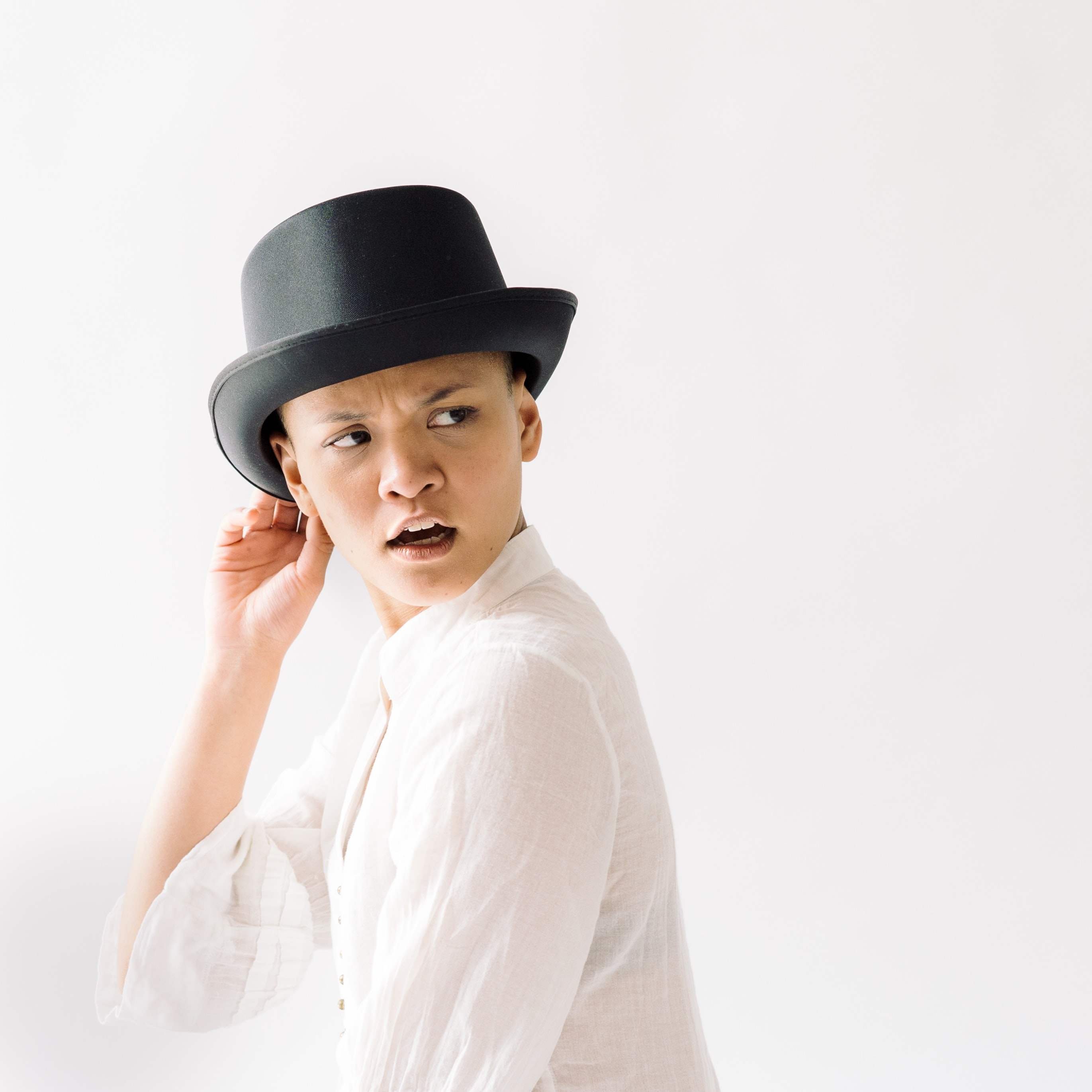 woman wearing top hat opening her mouth