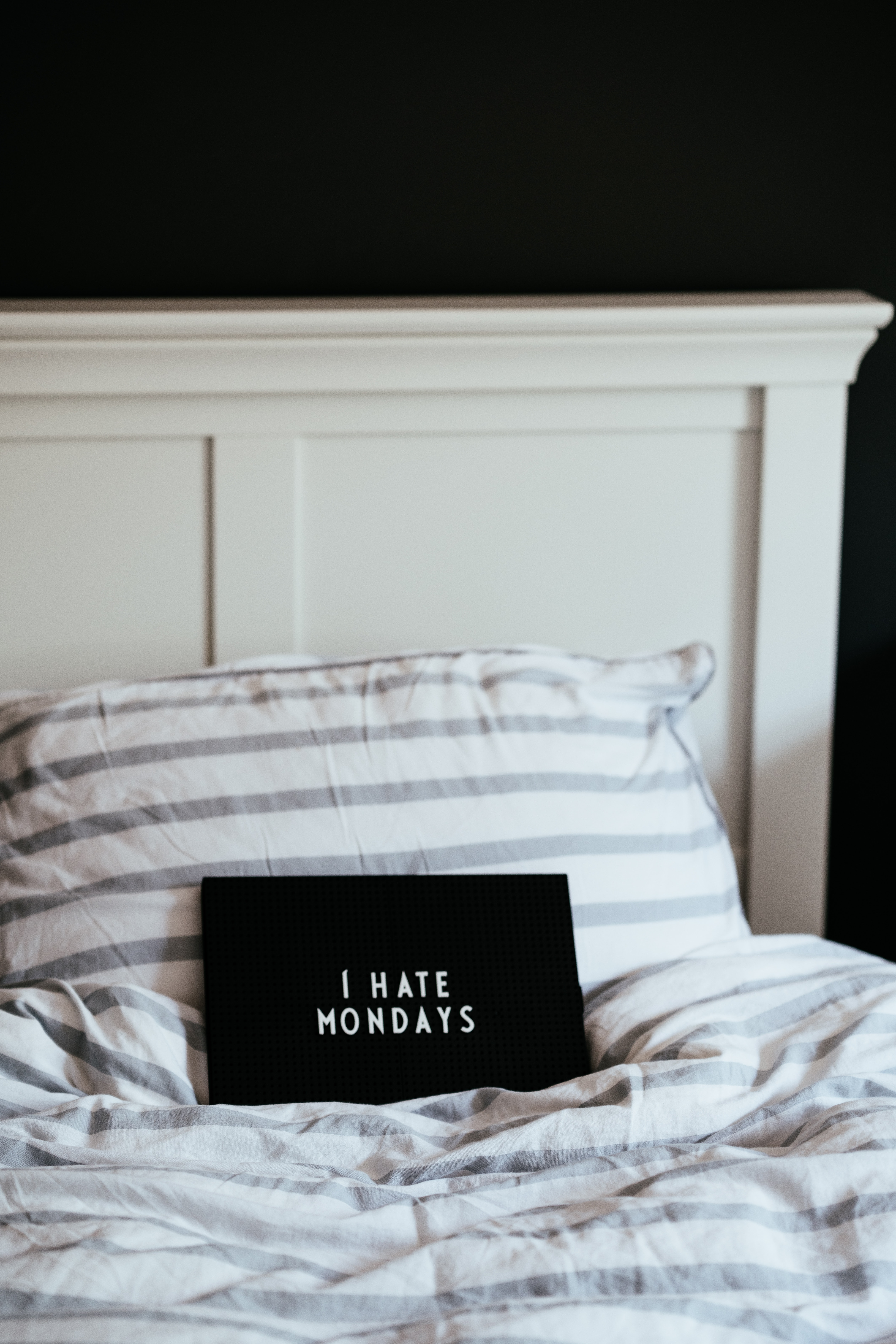 rectangular black i hate mondays-printed board on bed