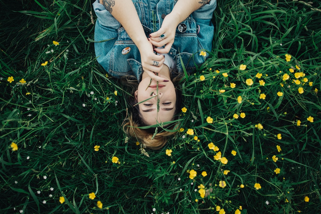 woman lying on grass ground with yellow petaled flowers