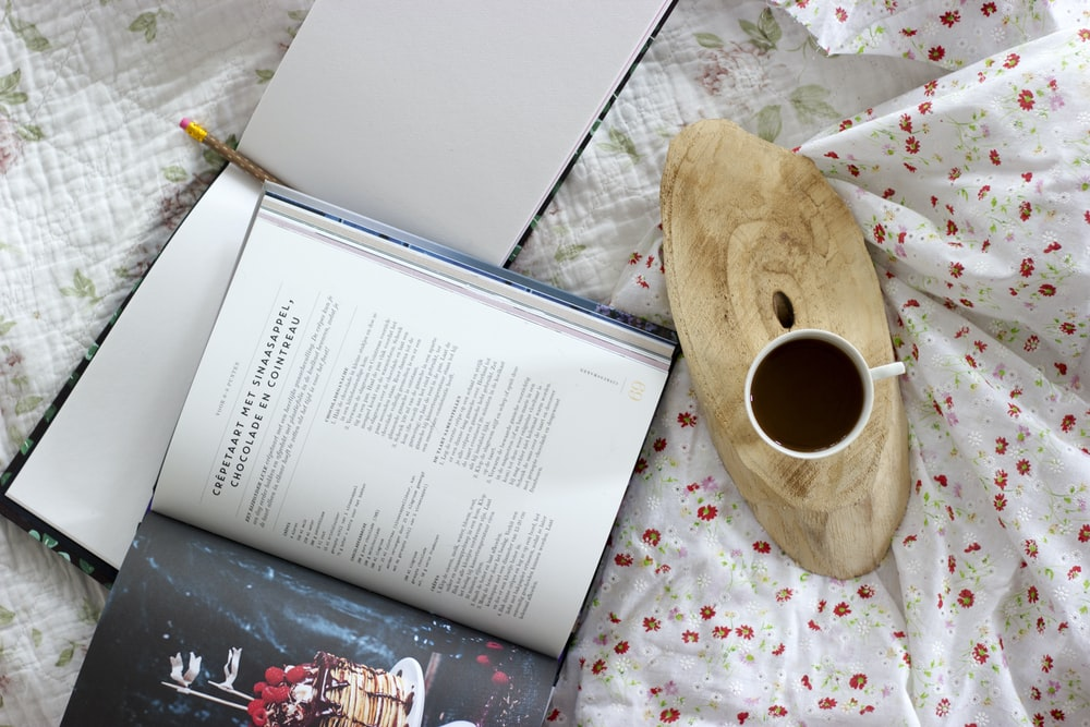 white ceramic mug beside opened book