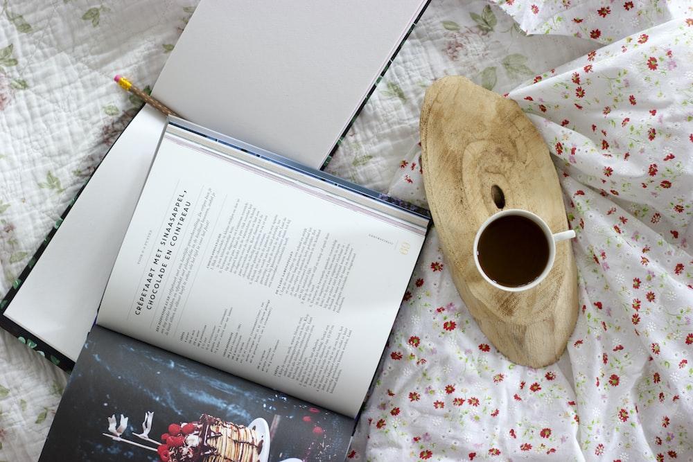 white ceramic mug beside opened book