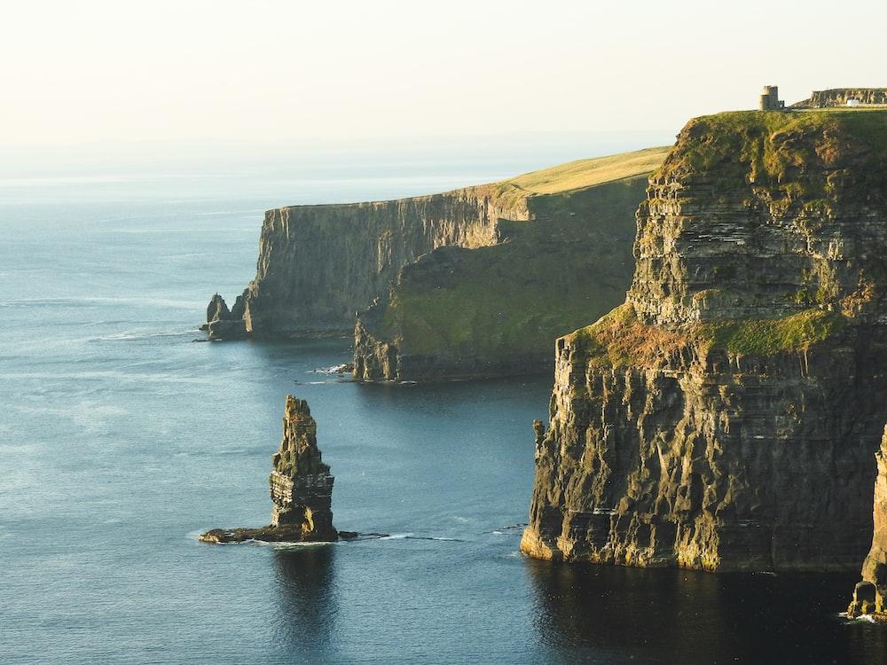 rock formation beside sea under white sky, cliffs of Moher on Irish coast