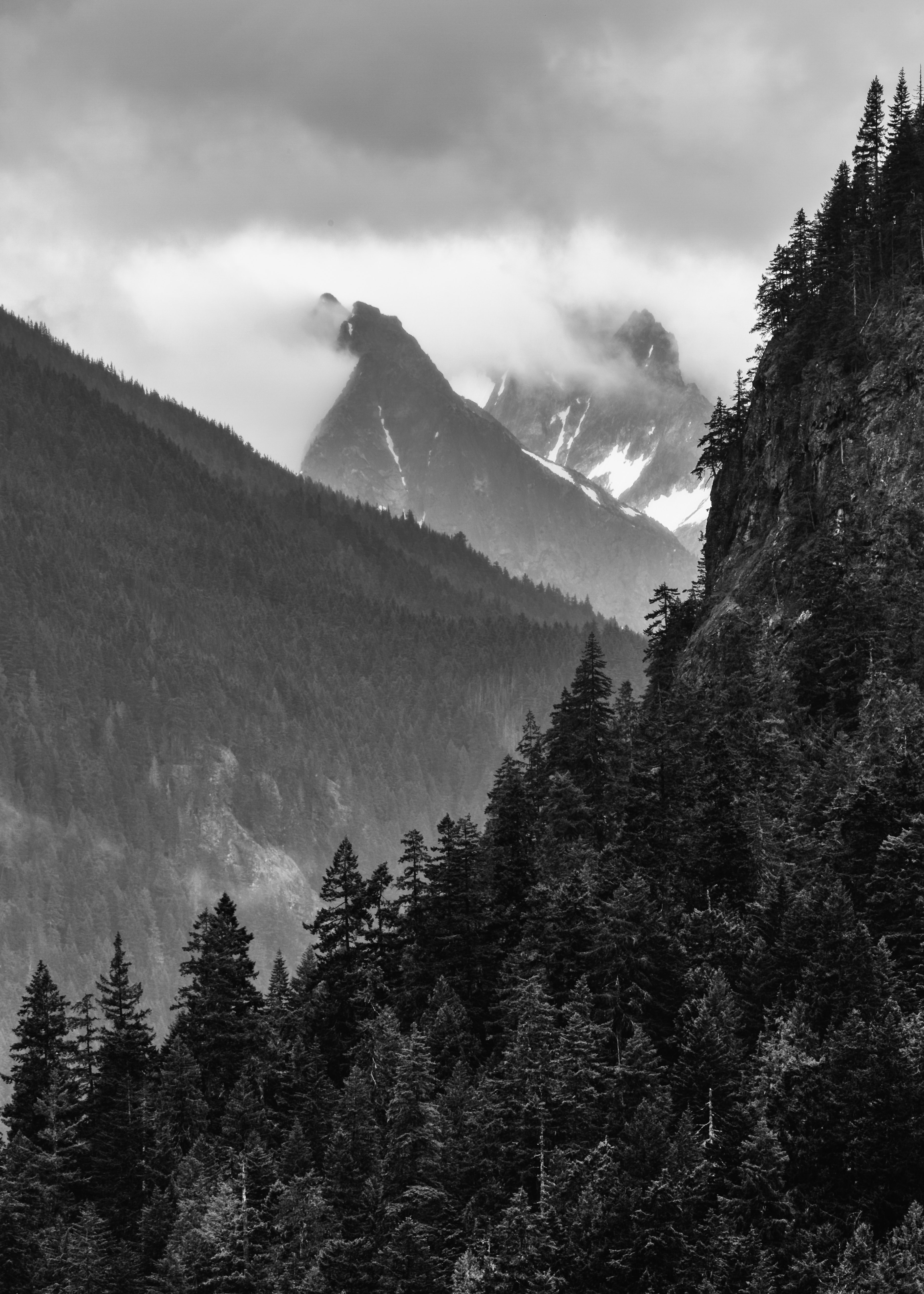 grayscale photo of mountains covered by clouds