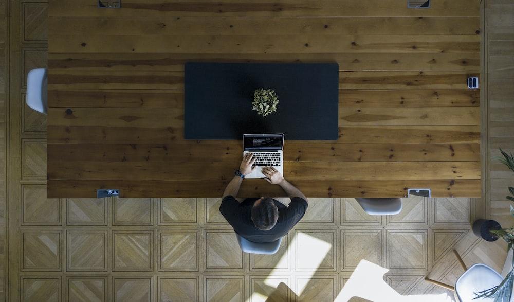 man wearing black shirt sitting on chair using laptop
