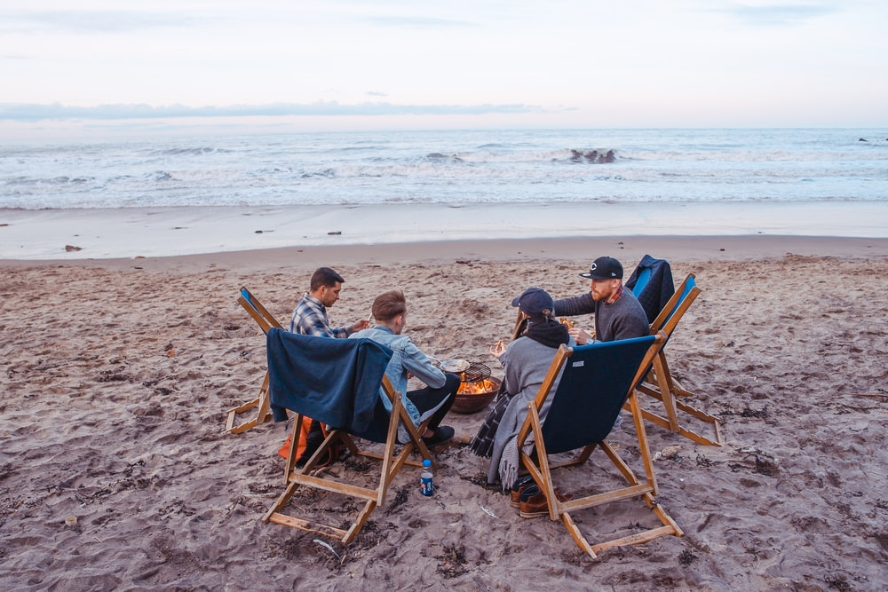 three men and one woman sitting on beach lounge in front fire pit near seashore