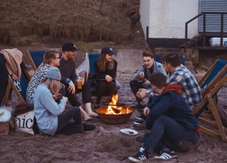 group of people sitting on front firepit