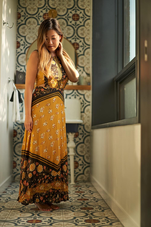 woman wearing floral dress standing near window