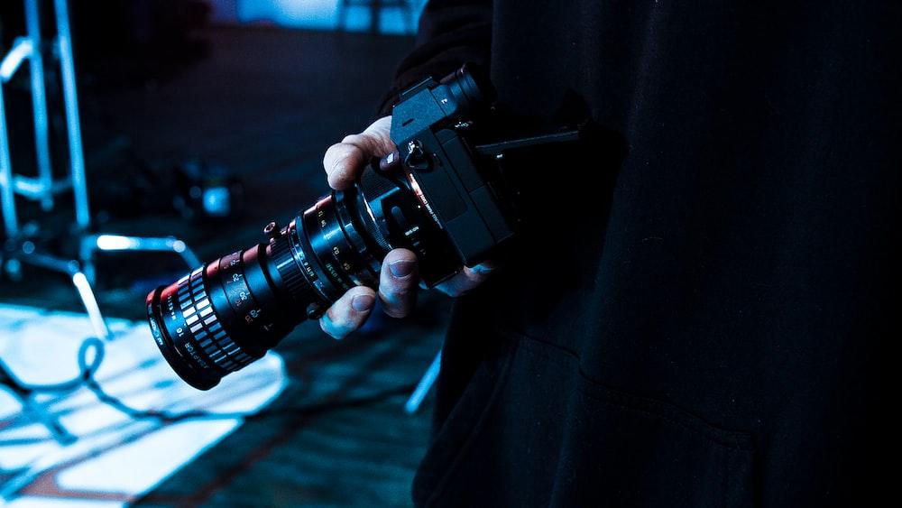 person holding black MILC camera
