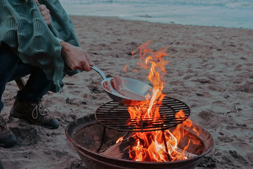 person cooking meat on bonfire near shoreline