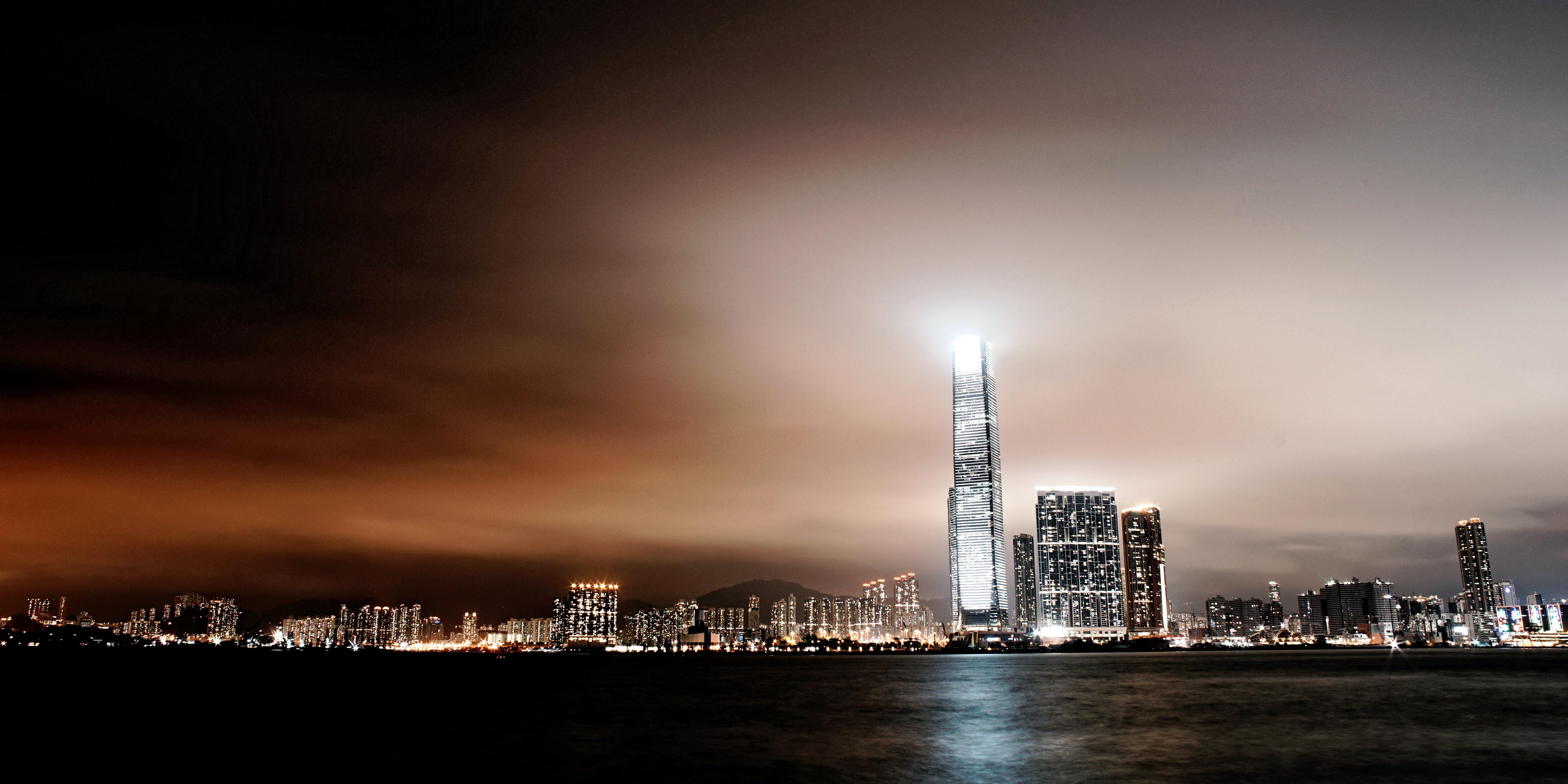 city skyline near body of water during nighttimne