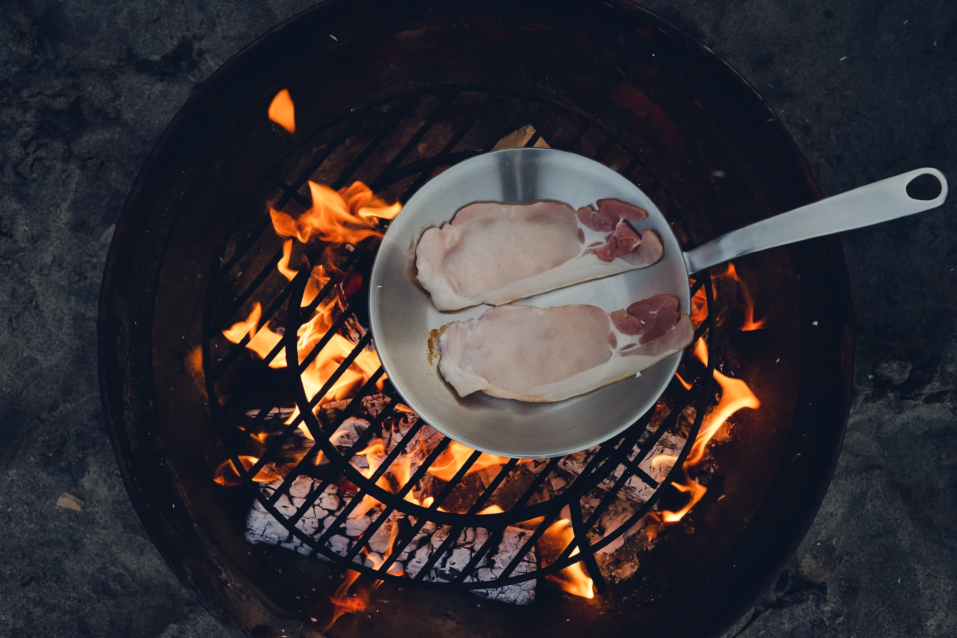 person cooking steak on charcoal gril
