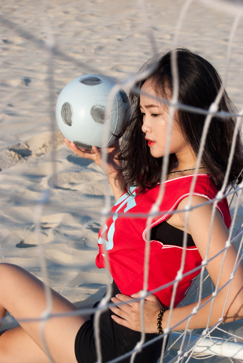 woman holding gray and black soccer ball