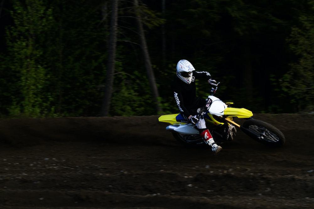 man ridding yellow and white motocross dirt bike