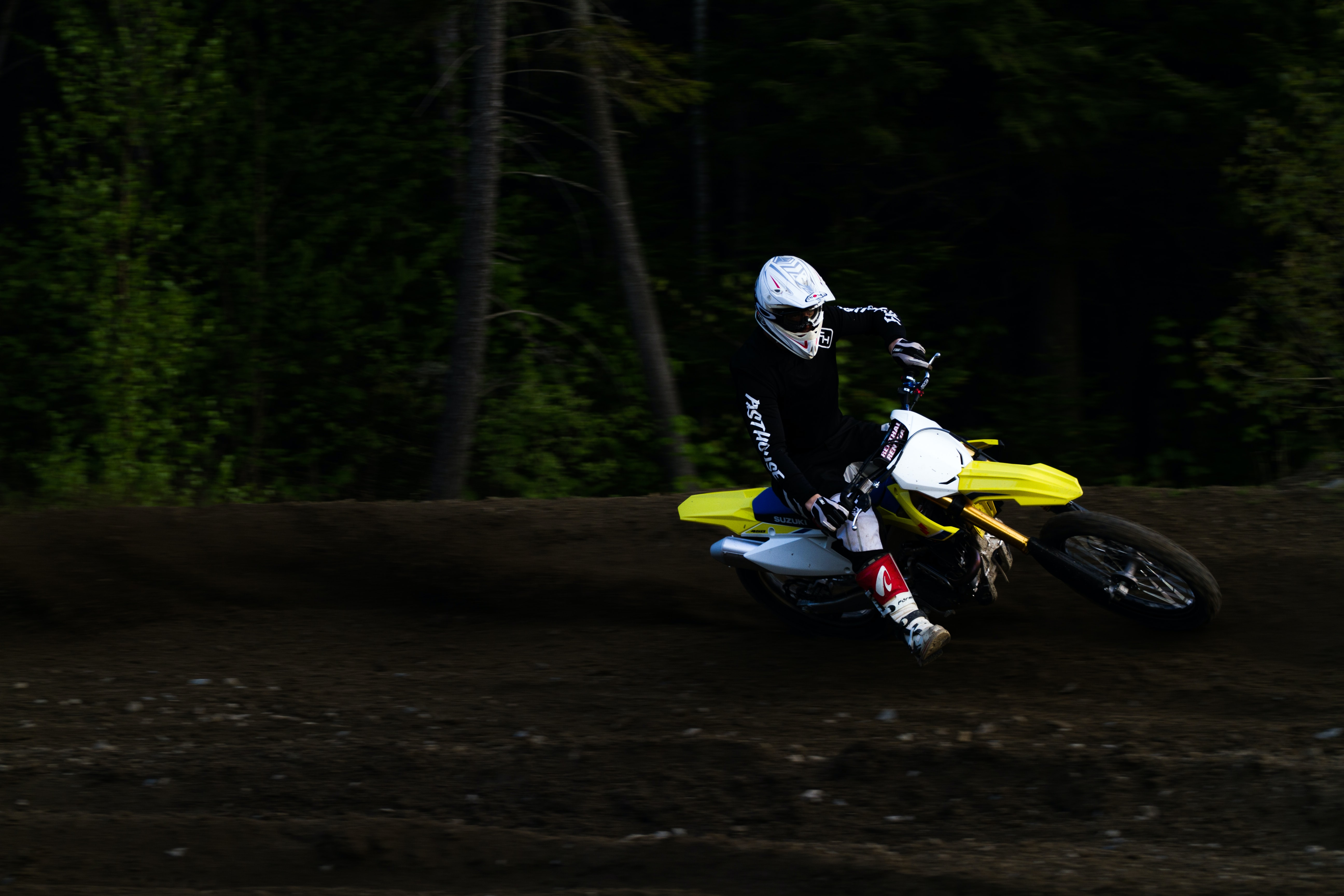man ridding yellow and white motocross dirt bike
