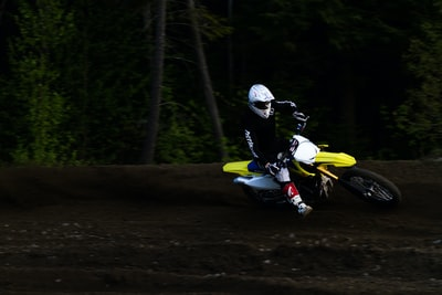 man ridding yellow and white motocross dirt bike trippy zoom background
