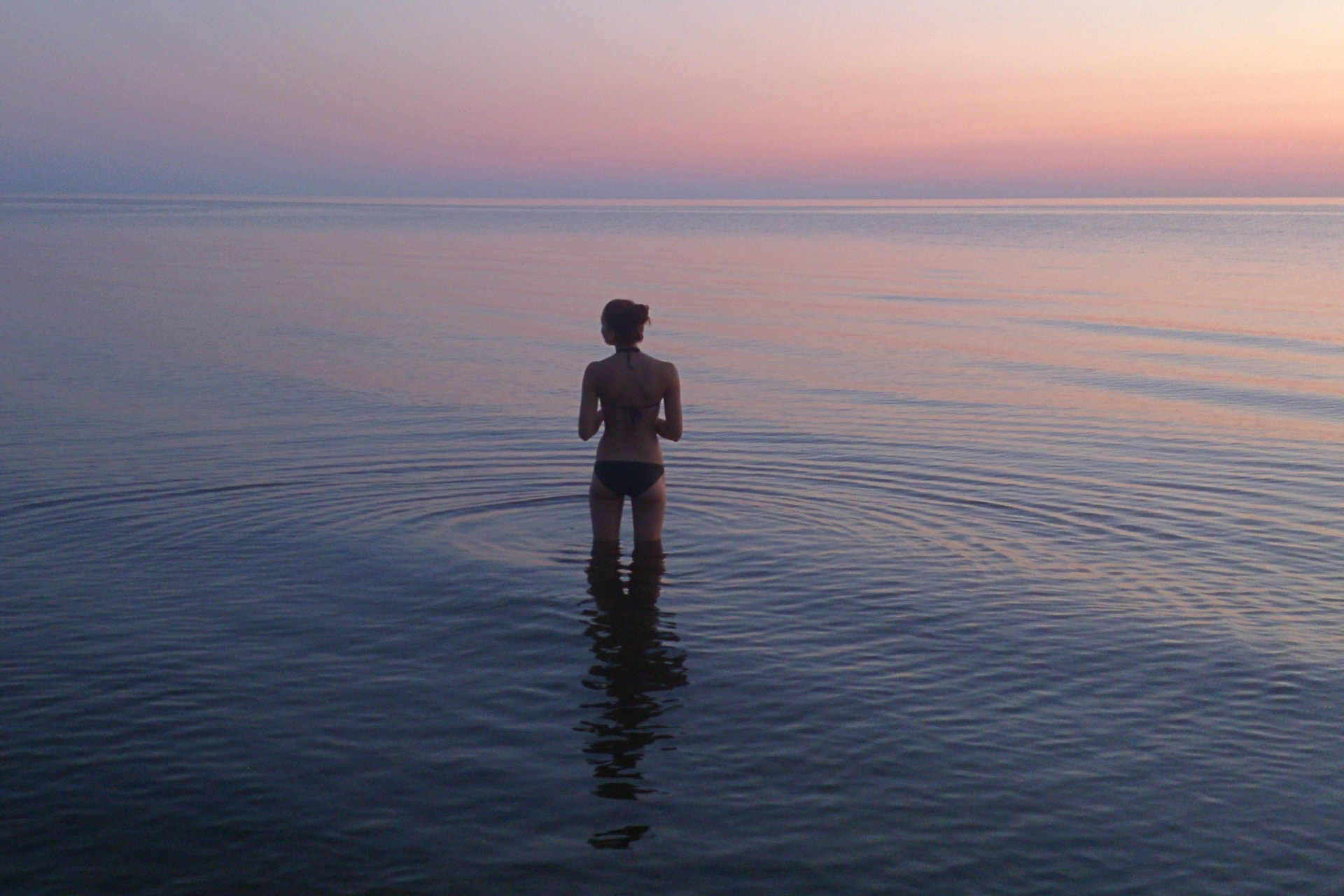 woman standing on body of water