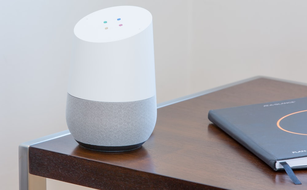 white and gray Google home on brown table