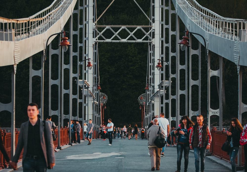 people walking and standing on bridge