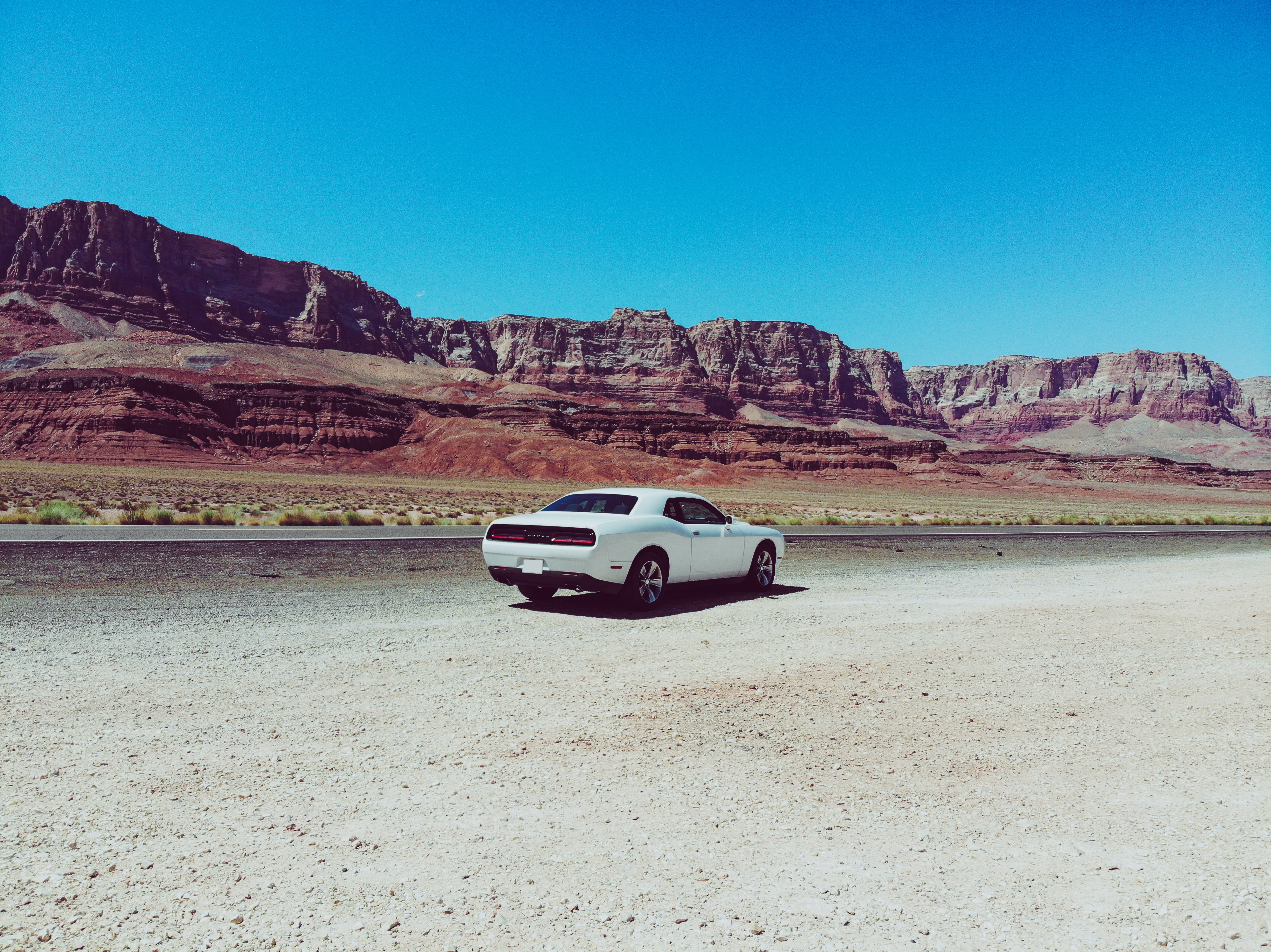 white coupe parked on desert field