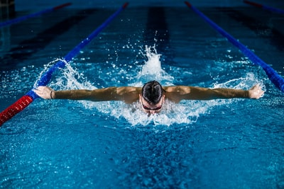 man doing butterfly stroke sports zoom background