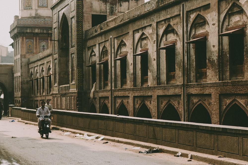 man riding motorcycle beside building during daytime